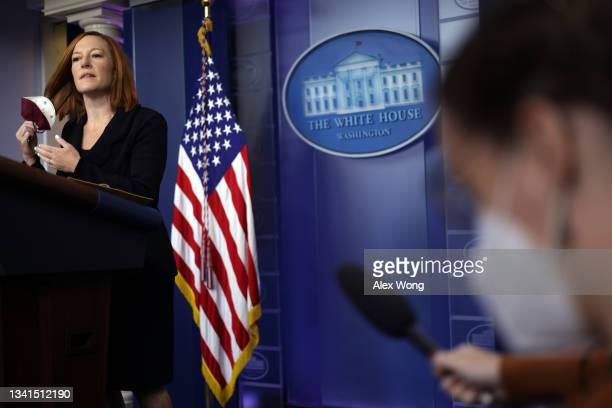 White House Press Secretary Jen Psaki takes off her mask as she arrives at the daily press briefing in the James S. Brady Press Briefing Room at the...