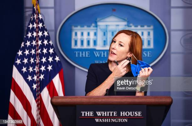 White House Press Secretary Jen Psaki takes off her mask at the start of a press briefing at the White House on October 18, 2021 in Washington, DC....