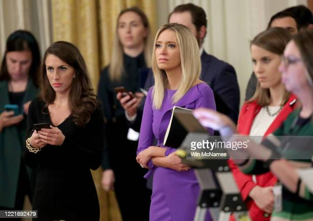 White House press secretary Kayleigh McEnany listens as U.S. President Donald Trump takes questions from reporters during an event on supporting...