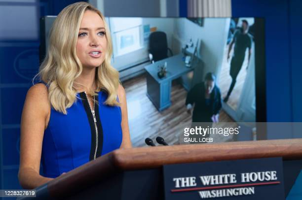 White House Press Secretary Kayleigh McEnany speaks while a video plays of Speaker of the House Nancy Pelosi walking into a hair salon as she holds a...