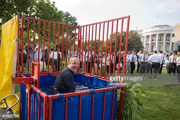 """White House Press Secretary Robert Gibbs is immersed in the """"dunking booth"""" by a ball thrown by a reporter before a luau on the South Lawn of the..."""