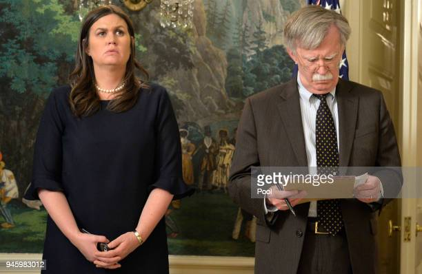 White House Press Secretary Sarah Huckabee Sanders and National Security Advisor John Bolton listen to remarks by US President Donald Trump as he...