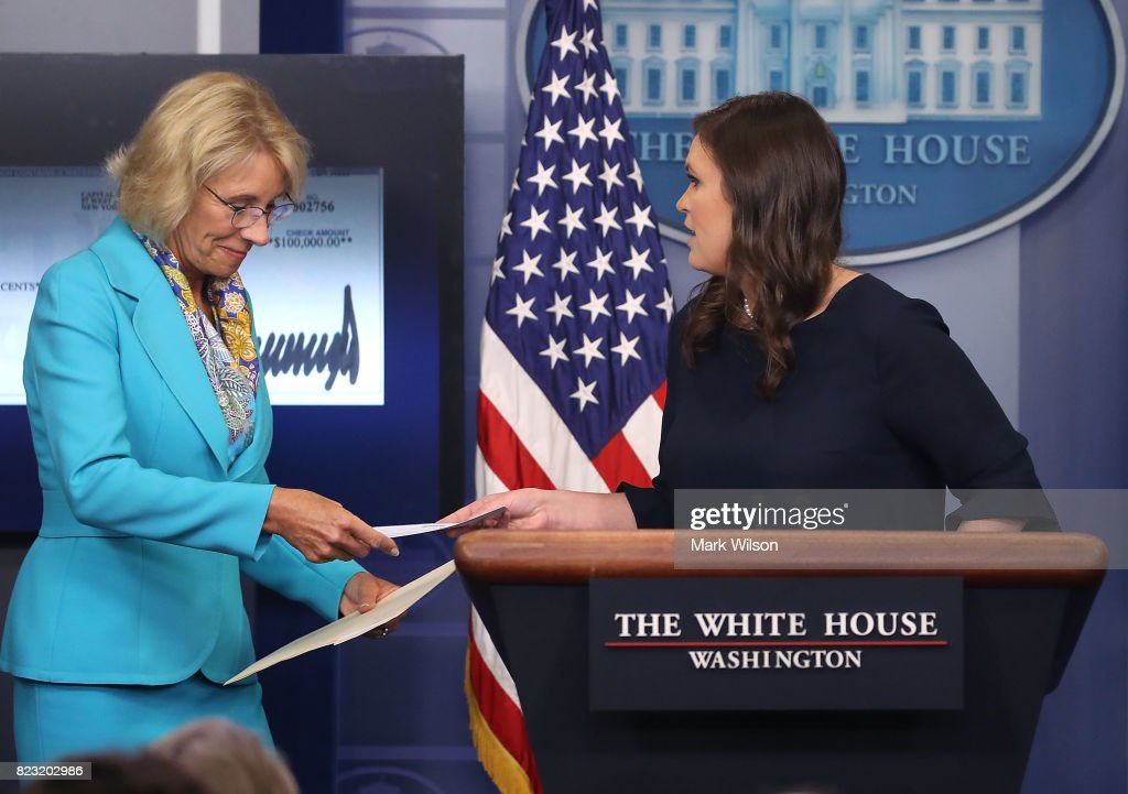 White House Press Secretary Sarah Huckabee Sanders (R) hands Secretary of Education Betsy DeVos a check from President Donald Trump to the Department of Education during the daily press briefing at the White House on July 26, 2017 in Washington, DC. President Trump donated his salary from the second quarter of the year to the Department of Education.
