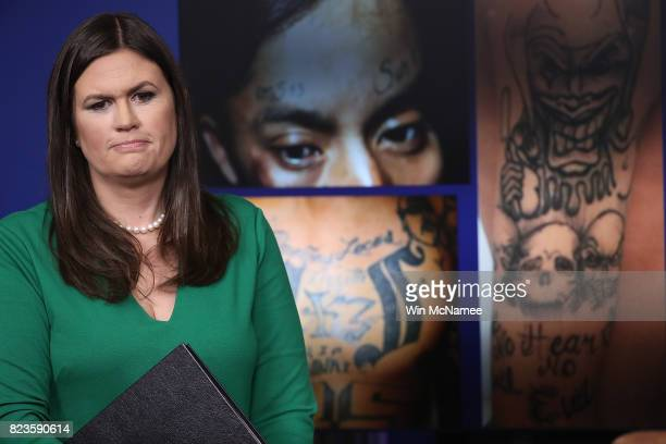 White House Press Secretary Sarah Huckabee Sanders stands in front of gang related photos from the MS13 gang during a daily briefing at the White...