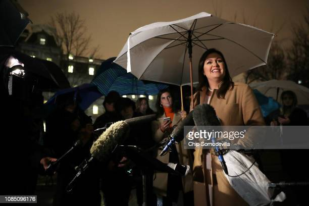 White House Press Secretary Sarah Huckabee Sanders talks to reporters in the rain outside the White House West Wing December 20 2018 in Washington DC...