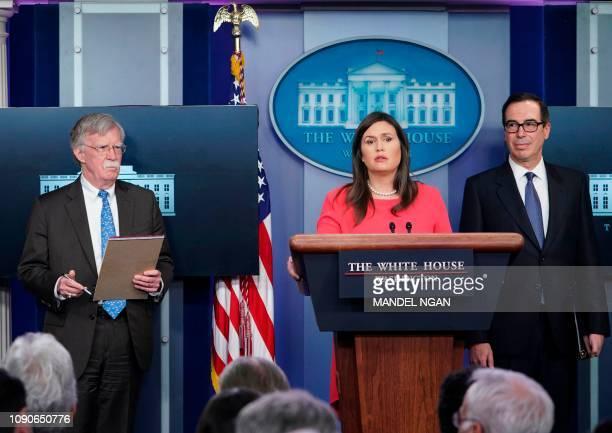 White House Press Secretary Sarah Sanders speaks as US Secretary of the Treasury Steven Mnuchin and National Security Advisor John Bolton look on...
