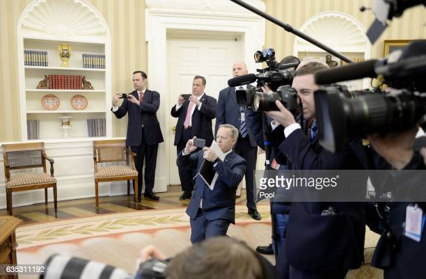 White House Press Secretary Sean Spicer and New Jersey Governor Chris Christie take pictures as US President Donald Trump signs HJ Res 41 in the Oval...
