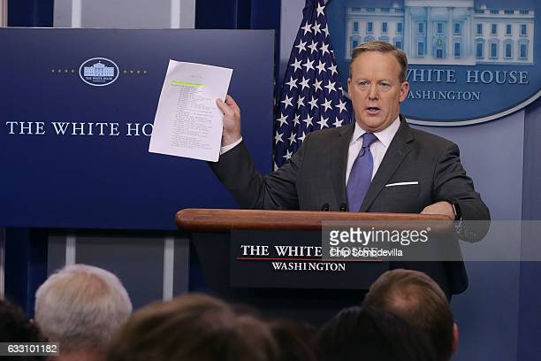 White House Press Secretary Sean Spicer holds up paperwork highlighting and comparing language about the National Security Council from the Trump...