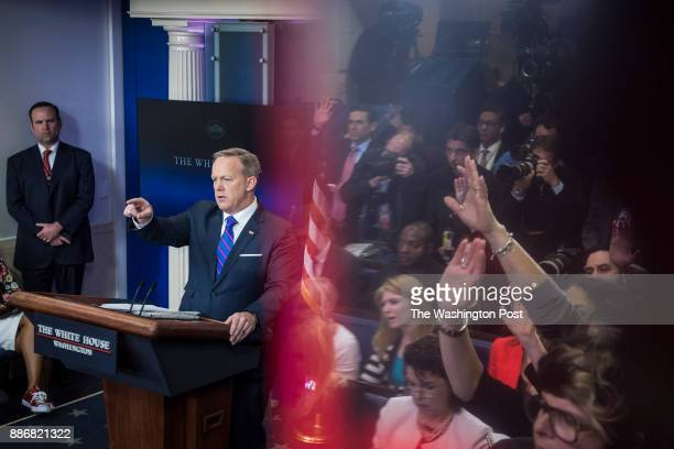 White House Press secretary Sean Spicer points as he answers questions from members of the media and reporters seen reflected in an exit sign during...