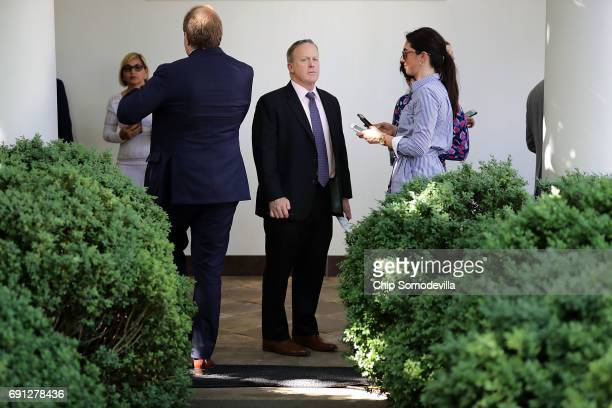 White House Press Secretary Sean Spicer stand in the Rose Garden Colonnade after President Donald Trump announced his decision to withdraw the United...