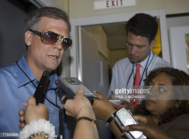 """White House Press Secretary Tony Snow briefs reporters 30 June 2006 aboard Air Force One, wearing a pair of """"Elvis sunglasses"""" as US President George..."""