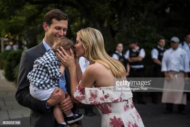 White House senior adviser Jared Kushner holds their son Theodore James Kushner as Ivanka Trump kisses him during the Congressional Picnic on the...