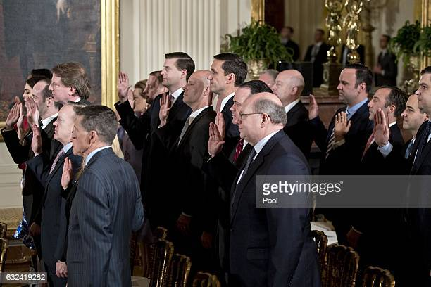 White House senior staff members are sworn in by US Vice President Mike Pence not pictured during a ceremony in the East Room of the White House on...