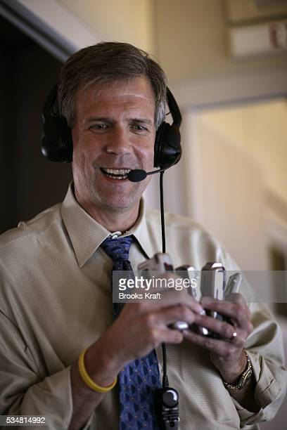 White House spokesman Tony Snow laughs as he holds on to reporters tape recorders while briefing the press aboard Air Force One before landing at...