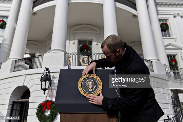 White House staff member adjusts the presidential seal before a tax bill passage event with US President Donald Trump not pictured and Republican...