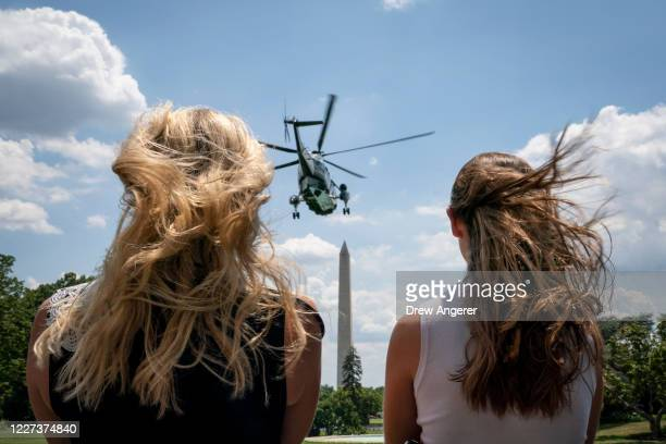 White House staff members watch as Marine One, with U.S. President Donald Trump onboard, takes off on the South Lawn of the White House on July 15,...