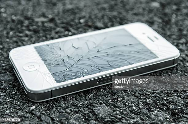 white iphone 4s with broken retina display laying on asphalt - broken stock photos and pictures