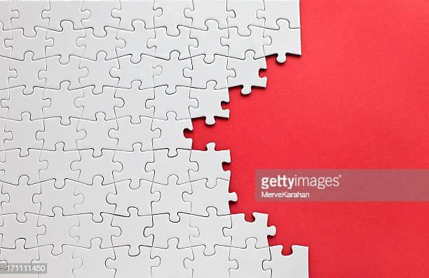 white jigsaw puzzle on a red background - raadsel stockfoto's en -beelden