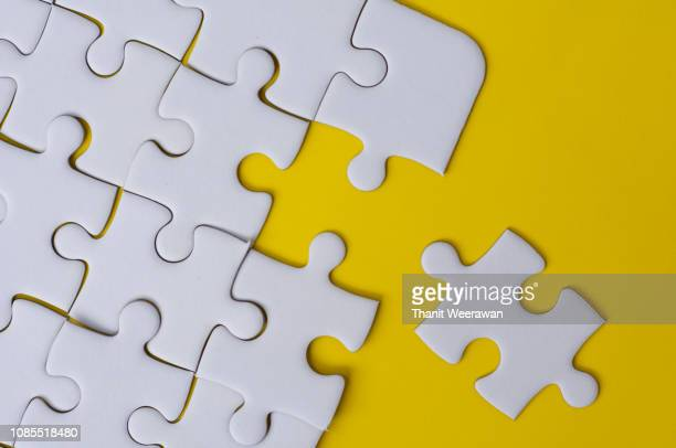 white jigsaw puzzle on yellow color background - link chain part stock photos and pictures