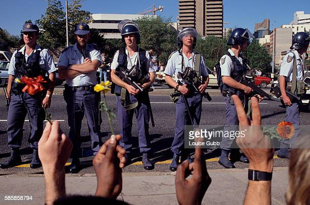 White Johannesburg riot police threaten antiapartheid student protesters at the University of Witwatersrand who are holding flowers and flashing...
