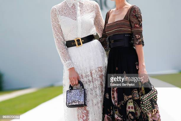 A white lace dress and a black dress with colored embroidery outside Dior during Paris Fashion Week Haute Couture Fall Winter 2018/2019 on July 2...