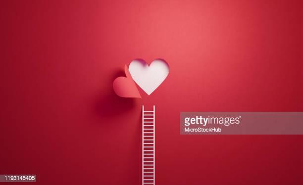witte ladder leunend op rode muur met uitgesneden hart vorm - romantiek begrippen stockfoto's en -beelden