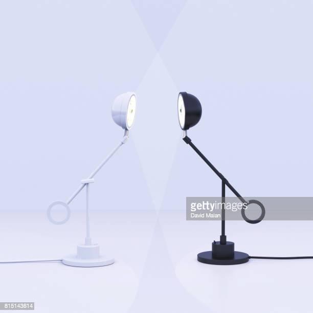 White lamp facing a black lamp.
