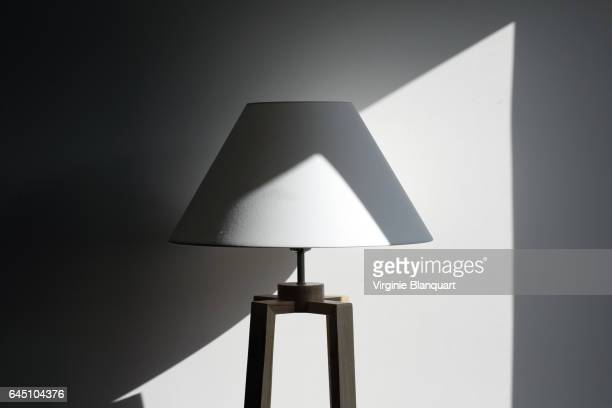 White lamp in front of a white wall in the sunlight and shadow