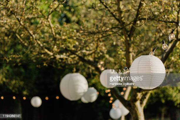white lanters on a wedding in a garden - garland decoration stock pictures, royalty-free photos & images