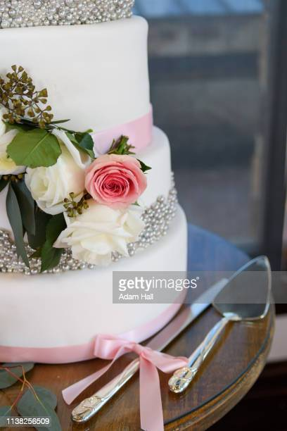 white layered wedding cake on a stand with rose flowers, beads, ribbon, knife and spatula - utah wedding stock pictures, royalty-free photos & images