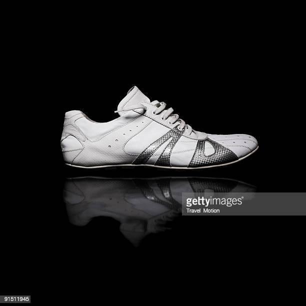 White leather fashion shoe on black reflective background