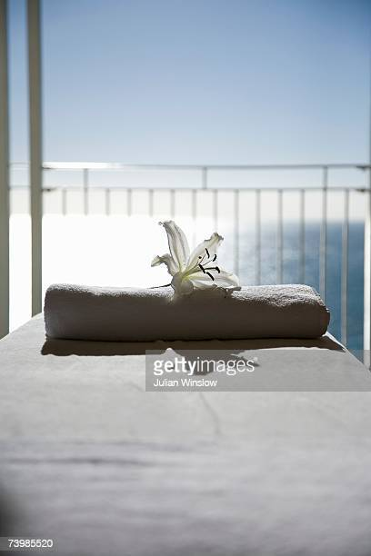A white lily and a folded towel on a massage table