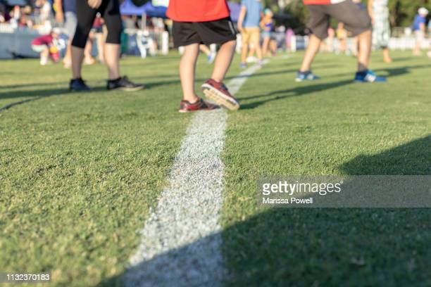 white line while people play - afl stock pictures, royalty-free photos & images
