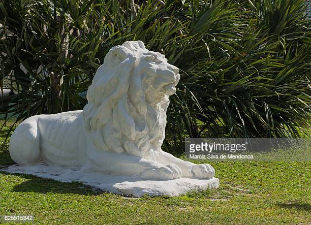 'A white lion statue on the grass'