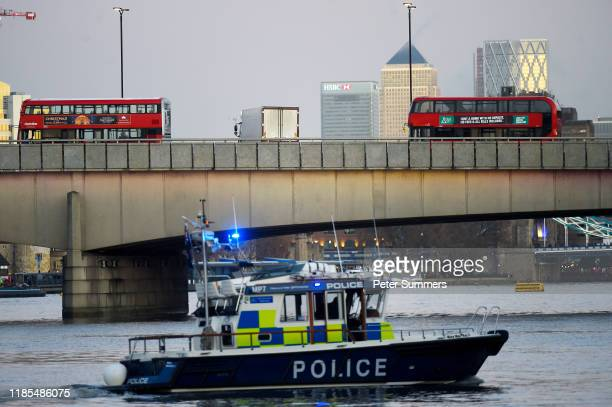 A white lorry is seen parked across London Bridge as boats from the Metropolitan Police Marine Policing Unit patrol near the scene after a number of...