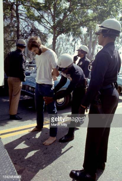 White man is arrested and searched by African-American Los Angeles Police officers during a student protest against President Richard Nixon's foreign...