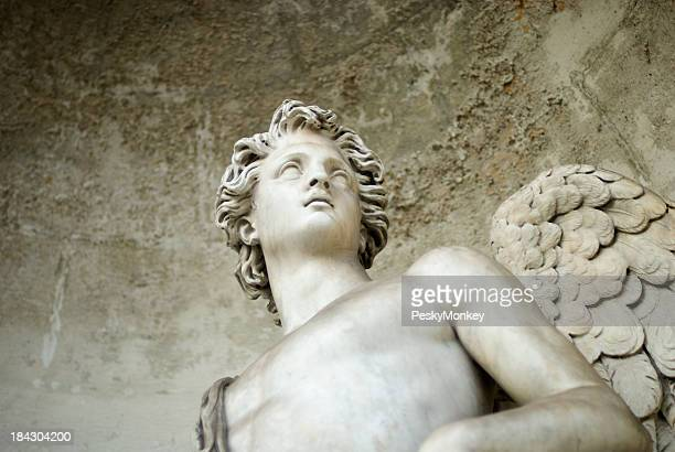 white marble angel looks out from stone alcove - male angel stock photos and pictures