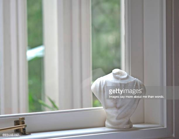 White marble bust by the window. Still life.