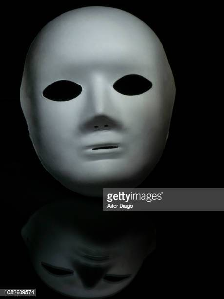 white mask on a reflective surface. light painting. conceptual nature - 殺人者 ストックフォトと画像