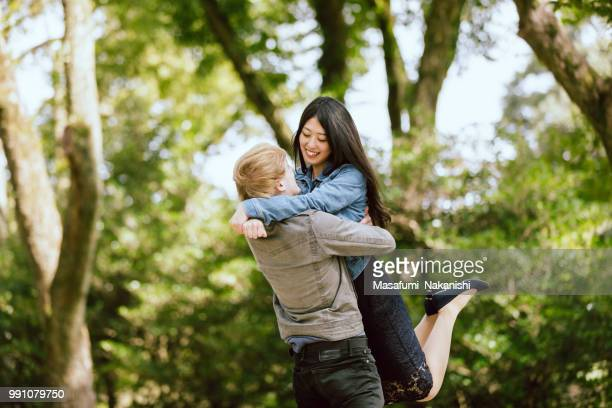 White men raising lovers who are Asian women at a fresh green park