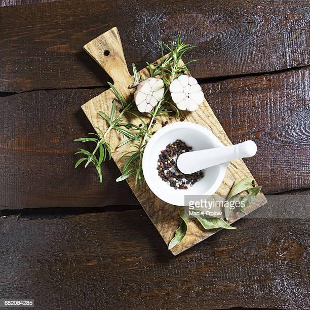 White mortar pepper grains, garlic and rosemary