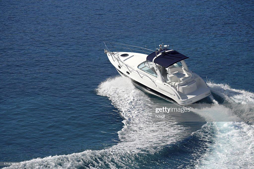 White motorboat making waves on blue water : Stock Photo