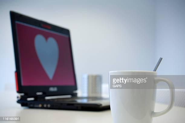 Weiße Tasse mit Herzform auf einem notebook