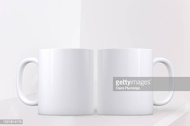white mug mockup. two white coffee mugs on a shelf with a white background. perfect for businesses selling mugs, just overlay your quote or design on to the image. - mug stock pictures, royalty-free photos & images