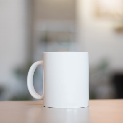 White mug on table and modern room background. Blank drink cup for your design. Can put text, image, and logo. 827626812