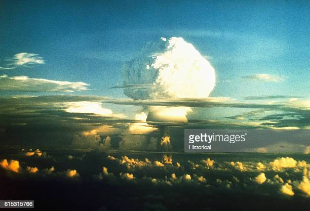 A white mushroom cloud from a thermonuclear bomb ascends through a layer of clouds during an atomic test in the Marshall Islands 1950