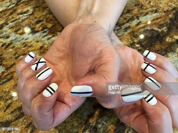 White nail varnish with black stripes