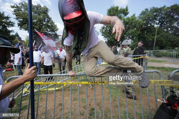 White nationalists neoNazis and members of the 'altright' leap over barricades inside Emancipation Park during the 'Unite the Right' rally August 12...