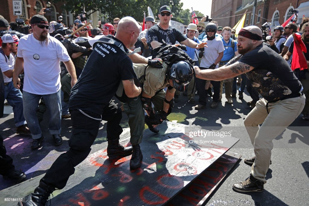 White nationalists, neo-Nazis, the KKK and members of the 'alt-right' attack each other as a counter protester (R) intervenes during the melee outside Emancipation Park during the Unite the Right rally August 12, 2017 in Charlottesville, Virginia. After clashes with anti-fascist protesters and police the rally was declared an unlawful gathering and people were forced out of Lee Park, where a statue of Confederate General Robert E. Lee is slated to be removed.