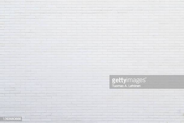 white new brick wall viewed from the front. - blanc photos et images de collection